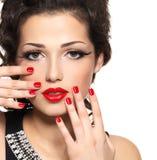 Beau modèle de mode avec la manucure et les languettes rouges Images stock