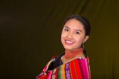 Beau modèle hispanique portant l'habillement traditionnel andin souriant et posant pour l'appareil-photo, fond jaune foncé photos stock