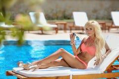 Beau modèle sexy de bikini de femme bronzé et se trouvant sur la chaise de plate-forme photographie stock libre de droits