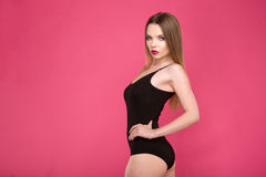 Beau modèle attrayant dans le maillot de bain noir posant sur le fond rose Photos libres de droits