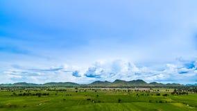Beau nuage et ciel bleu au-dessus de champ vert Photos libres de droits