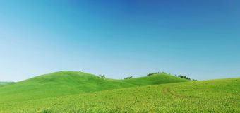 Beau panorama d'été avec les collines vertes et le ciel bleu Photographie stock libre de droits