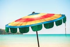 Beau parapluie de plage coloré de tissu rayé sur un fond de mer et de ciel Images libres de droits