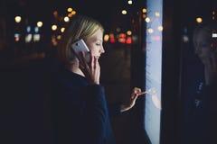Beau parler femelle blond au téléphone portable tout en touchant le grand écran numérique qui lumière se reflétante, Image libre de droits