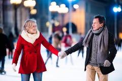 Beau patinage de glace supérieur de couples au centre de la ville L'hiver Image stock