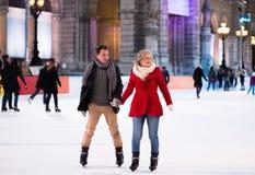 Beau patinage de glace supérieur de couples au centre de la ville L'hiver Photos libres de droits