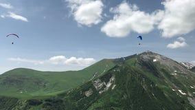 Beau paysage avec des parapentistes en montagnes vertes de Caucase banque de vidéos