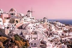 Beau paysage avec les bâtiments et les moulins à vent blancs de vintage à Oia sur l'île de Santorini, Grèce au coucher du soleil photographie stock