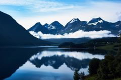 Beau paysage bleu avec les montagnes couronnées de neige et leur réflexion dans l'eau image libre de droits