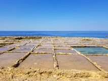 Beau paysage d'extraction de sel dans le rose et la couleur bleue sur l'île de Gozo, Malte photographie stock