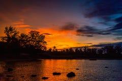 Beau paysage de coucher du soleil au-dessus de mer avec l'arbre de silhouette Photos stock