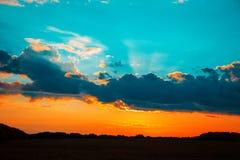 Beau paysage de flambage de coucher du soleil au-dessus derrière le pré et au ciel orange au-dessus de lui photographie stock libre de droits
