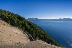 Beau paysage de la falaise volcanique avec des pins comme vu de la jante occidentale dans le lac crater Image libre de droits