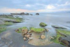 Beau paysage de lever de soleil par le bord de la mer rocheux Photos stock