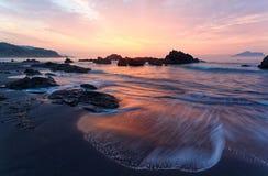 Beau paysage de lever de soleil par le bord de la mer rocheux Image stock