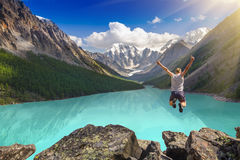 Beau paysage de montagne avec le lac et l'homme sautant Images stock
