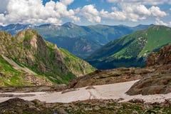 Beau paysage de montagne avec les pentes et la neige vertes Photos stock
