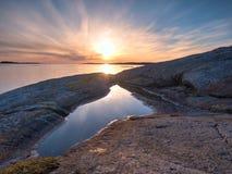 Beau paysage marin Refléter du coucher du soleil dans des piscines d'eau dans les roches Océan lisse images stock