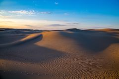 Beau paysage naturel de désert, dunes de sable sur le fond bleu de ciel de soirée photos stock
