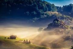 Beau paysage rural de montagne dans la lumière de matin avec le brouillard, les vieilles maisons et les meules de foin Photographie stock