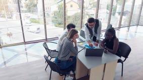Beau personnel élégant s'asseyant dans le bureau au bureau utilisant un ordinateur portable et écoutant un collègue banque de vidéos