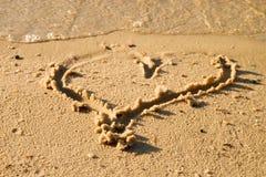 Beau petit coeur esquissé en sable de sel à la plage Photos stock