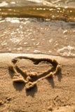 Beau petit coeur esquissé en sable de sel à la plage Même des couleurs chaudes de miroir de coucher du soleil dans le niveau d'ea Image stock