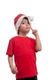 Beau petit garçon dans le chapeau de Santa Claus avec le doigt sur sa joue d'isolement sur le fond blanc Photographie stock
