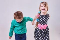 Beau petit garçon et fille tenant des mains et rire Photo libre de droits