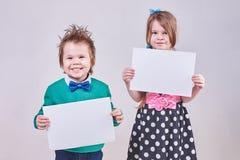 Beau petit garçon et fille tenant les feuilles de papier blanches photographie stock libre de droits