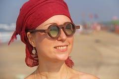 Beau phénomène de fille avec un brassard rouge sur sa tête, sur le fond de la mer Fille d'été en verres en bois ronds exceptionne image stock