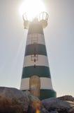 Beau phare avec le soleil lumineux sur le dessus sur le ciel Photos stock