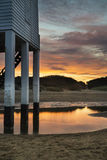 Beau phare d'échasse de lever de soleil de paysage sur la plage Photo stock