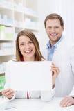 Beau pharmacien montrant un signe vide Photographie stock
