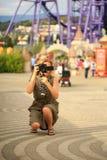 Beau photographe de femme faisant des photos en parc d'attractions Un blogger heureux fait une photo drôle pour son blog Image libre de droits