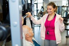 Beau physiothérapeute aidant la séance d'entraînement patiente supérieure avec des poids Image stock