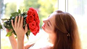 Beau plan rapproché de femme souriant et arome de reniflement des fleurs des roses rouges clips vidéos
