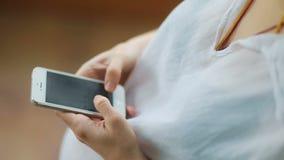 Beau plan rapproché de la jeune femme enceinte tapant sur son smartphone sur la vidéo animée lente de Steadicam de fond en bois banque de vidéos
