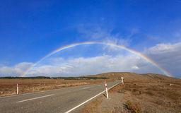 Beau plein double arc-en-ciel au-dessus de route photographie stock libre de droits