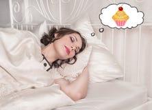 Beau plus la femme de taille dormant et rêvant du gâteau Photographie stock