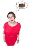 Beau plus la femme de taille en verres rêvant du gâteau Image stock