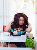 Beau plus la femme de taille redresse ses cheveux, café image stock