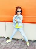 Beau port d'enfant de petite fille lunettes de soleil et vêtements de jeans Image stock