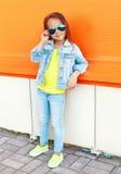 Beau port d'enfant de petite fille lunettes de soleil et vêtements de jeans au-dessus de coloré Photographie stock libre de droits