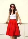 Beau port de sourire de femme de brune lunettes de soleil et jupe rouges photographie stock libre de droits