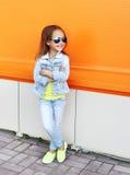 Beau port de sourire de petite fille lunettes de soleil et vêtements de jeans Photographie stock libre de droits