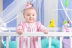 Beau portrait d'une petite fille dans une robe rose dans une crèche photo stock