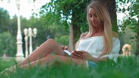 Beau portrait de jeune femme lisant un livre sous un arbre en parc banque de vidéos