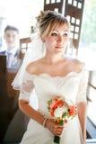 Beau portrait de jeune mariée avec le marié derrière le verre, épousant le bouquet dans des mains à l'intérieur image libre de droits