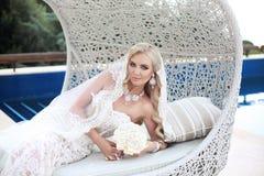 Beau portrait de jeune mariée tenant le bouquet de mariage posant dans la dentelle Image stock